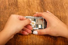 Change of the SIM card in a smartphone. On wooden table. female hands insert a SIM card in the phone Stock Image