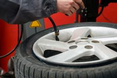 Change a tire, Car mechanic is changing a tire. In a garage Stock Photos
