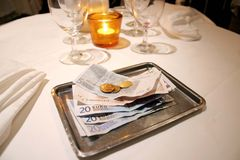 Change on a tray. A picture of a table in a restaurant, with a closeup on the tray with the change after the bill's been paid Royalty Free Stock Photo