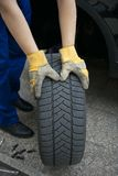 Change of tyres. An auto mechanic and changing tires Stock Image