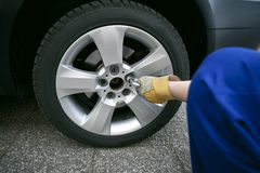 Change of tyres. An auto mechanic and changing tires Stock Photo