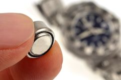 Change a watch battery. Close-up of an electric pile with a blurred watch in the background stock photo