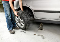 Change Wheel. A male changing a tire on a car in a garage royalty free stock photos