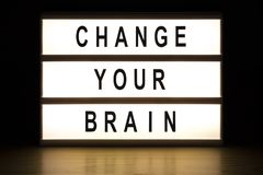 Change your brain light box sign board. On wooden table stock photo