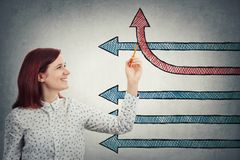 Change your direction. Young businesswoman drawing arrows, one of them change the direction and go up, as a progress graph. Business change and growth symbol stock photos