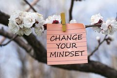 Change your mindset in memo. Pined on tree with blooms royalty free stock photo