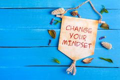 Change your mindset text on Paper Scroll. With dried flower around and blue wooden background royalty free stock images