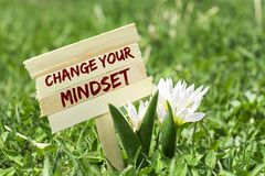 Change your mindset. On wooden sign in garden with white spring flower royalty free stock photo