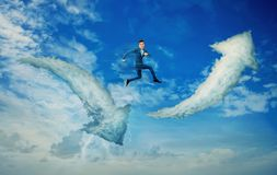 Change your way. Surreal view as a businessman jump from one cloud to another. Clouds in shape of arrows going up and down, over a blue sky background. Changing Royalty Free Stock Photos