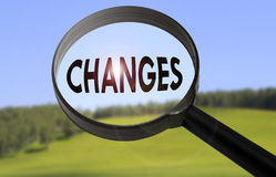 Changes. Magnifying glass with the word changes on blurred nature background. Searching changes concept Stock Images