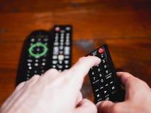 Changez la chaîne de télévision avec le doigt dans à télécommande images stock