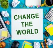 changez le monde Le bureau de table de bureau avec des approvisionnements, bloc-notes vide blanc, tasse, stylo, PC, a chiffonné l Images stock