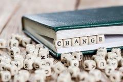 Changez le mot écrit sur un bloc en bois Photographie stock libre de droits