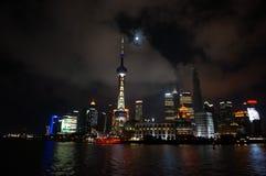 Changhaï la nuit par Bund avec la pleine lune et les nuages Photo stock