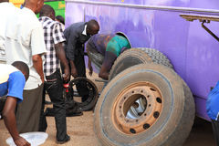 Changing a Bus Tire and Brakes in Africa. MBARARA, UGANDA - SEPTEMBER 27, 2012. A bus maintenance worker changes the back tires and brakes of  broken down Royalty Free Stock Photo