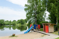 Changing cabin and water slide at beach shore Stock Photography