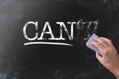 Changing CANT to CAN by erasing letter T with blackboard eraser. Motivation concept stock image