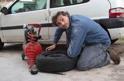 Changing car tire. Man changing the spare tire stock photo