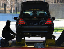 Changing Car Tires. A mechanic installs new tires on a car Stock Images