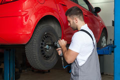 Changing the Car Wheel With an Impact Wrench Royalty Free Stock Image