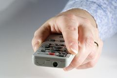 Changing the Channel. Hand holding a remote control Royalty Free Stock Photography