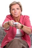 Changing channels. Woman with remote control changing channels stock images