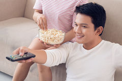 Changing channels. Smiling young men changing tv channels with remote control royalty free stock photo