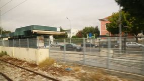 Changing cityscape viewed from the moving train with railway track running along. Stock footage stock video