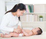 Changing diaper. Asian mother changing diaper to baby girl at home Stock Photos