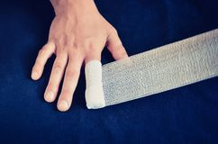 Changing dressing on hands. Wrap the bandage on the finger wound royalty free stock image