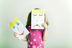 Changing Emotions. Little blonde girls holding happy and sad face masks symbolizing changing emotions Royalty Free Stock Images