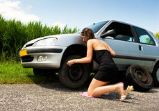 Changing a flat tire. Young woman, kneeling to tighten the bolts on a spare tire Royalty Free Stock Photo