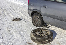Changing a flat tire. In the winter snow with backup Stock Photos