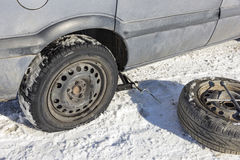 Changing a flat tire. In the winter snow with backup Royalty Free Stock Images