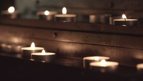 Church table for candles. Changing the focus from the candles in the foreground, at the bottom of the table, to the candles in the background at the top of the stock footage
