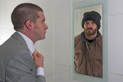 Changing Fortunes. Business Man looking in the mirror and seeing a Tramp staring back in the reflection Royalty Free Stock Images