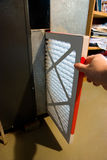 Changing Furnace Filter. Close up of hand changing home furnace filter Stock Photo