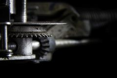 Changing Gears. A gearing mechanism from a classic 1940`s typewriter with bokeh to faded black background. Suitable for business and industry advertising Royalty Free Stock Photos