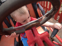 Changing gears. Little boy sitting behind the wheel of an immobile car truck in a playground Stock Image
