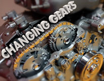 Changing Gears Shifting Topic Car Vehicle Engine. Changing Gears in 3d letters on a car, auto or vehicle engine to illustrate shifting a topic or increasing Royalty Free Stock Image