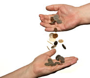 Changing Hands. Coins dropping from on hand to another isolated on white background royalty free stock photo