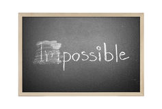 Changing impossible into possible on a chalkboard Royalty Free Stock Image