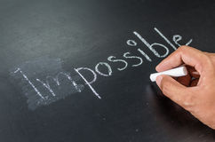 Changing impossible into possible on a chalkboard Royalty Free Stock Images