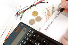 Changing impossible word to possible, calculator, charts, pen in hand, money. Workplace businessman Royalty Free Stock Photography