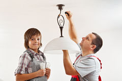 Changing the incandescent lightbulb with a fluorescent one. Changing an incandescent lightbulb with a fluorescent one - boy helping his father Royalty Free Stock Photo
