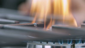 Changing the intensity of fire on gas cooker. Close up shots of kitchen activities while turning on and off fire on gas cooker cooktop stock footage