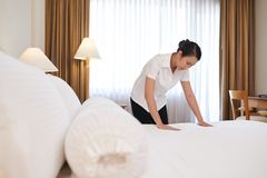 Changing linen. Chambermaid changing linen in the hotel room Stock Image