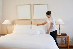 Changing linen. Maid changing linen in hotel room in the morning Royalty Free Stock Photo