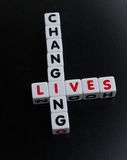 Changing lives. Text ' changing lives ' inscribed in uppercase letters on small white cubes arranged crossword style with common letter ' i ' , dark background Royalty Free Stock Photography