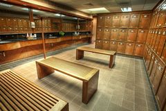 Changing or locker room in a country club. An interior shot of a locker or changing room at a golf and country club with wooden made lockers and benches for male Royalty Free Stock Photo